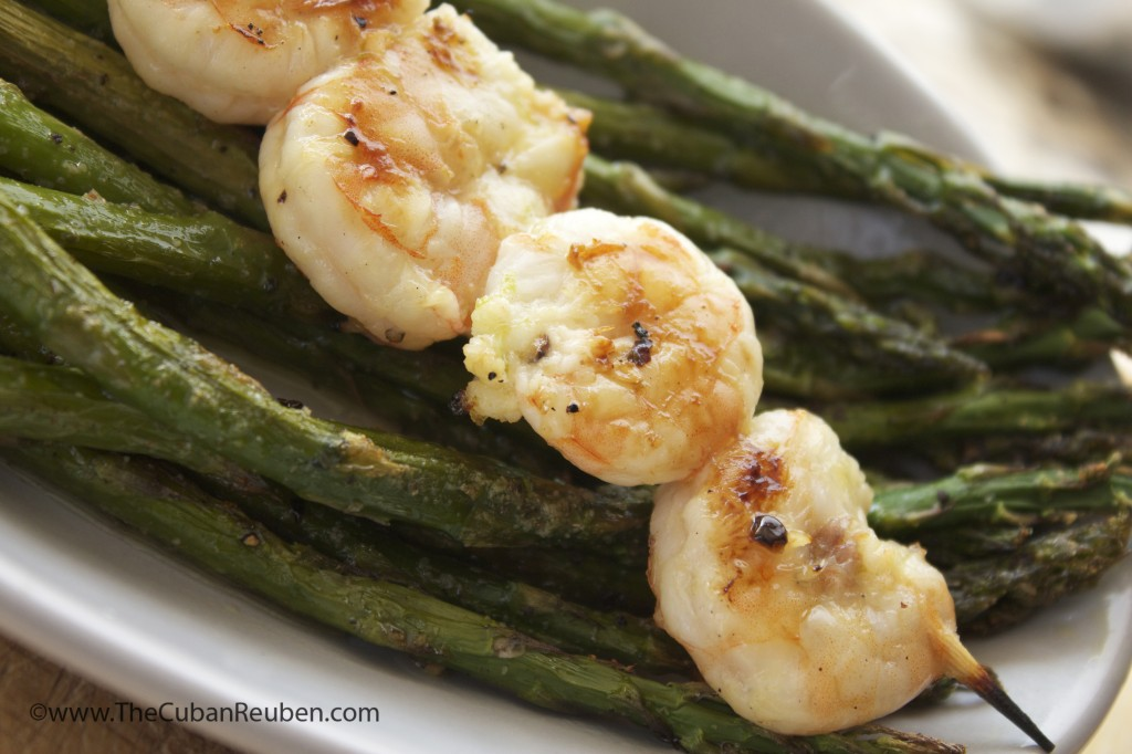 Grilled honey lime shrimp, resting on a bed of charred asparagus.