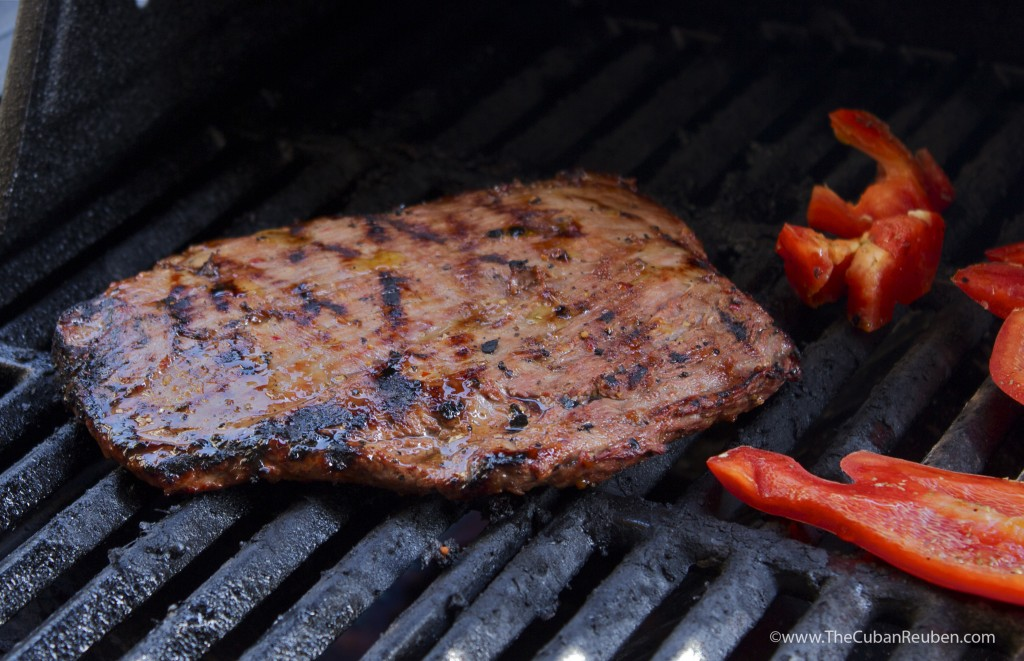 Marinated flank steak sizzling on the grill with bell pepper pieces.